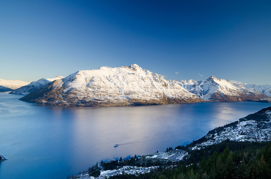 Snow covered Walter and Cecil Peaks at sunset with the Earnslaw returning to Queenstown on Lake Wakatipu, South Island, New Zealand