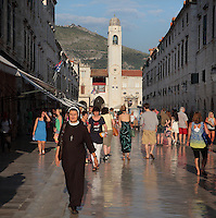 Stradun or Placa, the main street in the Old Town, with bell tower behind, Dubrovnik, Croatia. The street is 300m long and paved in limestone. The city developed as an important port in the 15th and 16th centuries and has had a multicultural history, allied to the Romans, Ostrogoths, Byzantines, Ancona, Hungary and the Ottomans. In 1979 the city was listed as a UNESCO World Heritage Site. Picture by Manuel Cohen