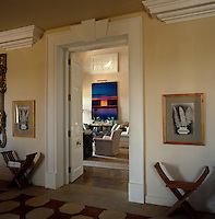 The door to the living room is flanked by an identical pair of stools, above which hangs a pair of prints