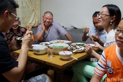 Former farmers dine in southern China in their newly furnished apartment given by the government in return for seized land.<br /> <br /> China is pushing ahead with a dramatic, history-making plan to move 100 million rural residents into towns and cities over six years &mdash; but without a clear idea of how to pay for the gargantuan undertaking or whether the farmers involved want to move.<br />