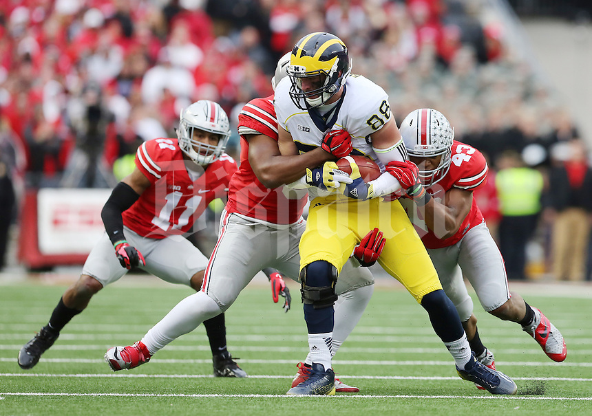 Ohio State Buckeyes linebacker Darron Lee (43), linebacker Raekwon McMillan (5), and defensive back Vonn Bell (11) stop Michigan Wolverines tight end Jake Butt (88) after he made a catch during the 4th quarter of the NCAA football game at Ohio Stadium on Nov. 29, 2014. (Adam Cairns / The Columbus Dispatch)