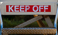 "A weather beaten, worn ""keep off"" sign at a lifeguard station at Crystal Cove State Park."