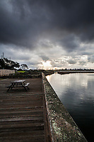 The railing on the fishing dock at MLK Regional Shoreline stretched west, toward a break in the storm clouds.