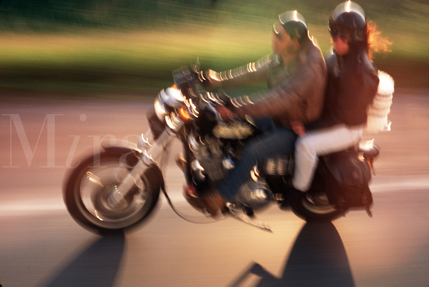 Blurred action image of a couple riding on a motorcycle.