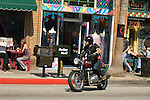 Motorcylcist passes shops and cafes along Abbot Kinney Blvd. in Venice, California