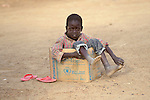 A boy sits in an emergency food rations box in Agok, a town in the contested Abyei region where tens of thousands of people fled in 2011 after an attack by soldiers and militias from the northern Republic of Sudan on most parts of Abyei. Although the 2005 Comprehensive Peace Agreement called for residents of Abyei--which sits on the border between Sudan and South Sudan--to hold a referendum on whether they wanted to align with the north or the newly independent South Sudan, the government in Khartoum and northern-backed Misseriya nomads, excluded from voting as they only live part of the year in Abyei, blocked the vote and attacked the majority Dinka Ngok population. The African Union has proposed a new peace plan, including a referendum to be held in October 2013, but it has been rejected by the Misseriya and Khartoum. The Catholic parish of Abyei, with support from Caritas South Sudan and other international church partners, has maintained its pastoral presence among the displaced and assisted them with food, shelter, and other relief supplies.