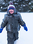 Laughing little boy running in the snow winter outdoor nature scenic. Blurred from motion.