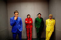"""Los Angeles, California, November 27, 2010 - A portrait of the band Ok Go, from left, lead singer/guitarist, Damian Kulash (blue), guitarist/singer, Andy Ross (red), drummer, Dan Konopka (green), and bass guitarist/singer, Tim Nordwind (yellow), in a freight elevator at the Nokia Club. OK Go was wrapping up a 16-month world tour by playing a song for Yo Gabba Gabba! during the day and later a final show at the Nokia Club. The Grammy Award-winning band has earned considerable fame for their creative, often low-budget music videos that are released on YouTube. Many have gone viral, including the 2006 video for """"Here It Goes Again"""", where the band performs a complex routine on treadmills. It has received over 50 million views to date. Kulash says the band left their major label and began their own to assert more creative control over their music and their videos. Adding, """"We're among the first musicians to view our YouTube videos as standalone artistic output, not advertisement for our recordings, and it shows in the numbers: over the past decade, we've sold a little over 600,000 records globally, and our videos have combined views in excess of 125 million.""""."""