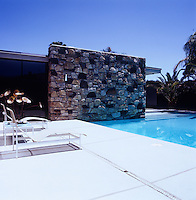 A natural rock wall of the house merges into the water of the swimming pool