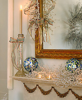 On a mantelpiece in the living room gold ribbon, candlelight and icy blue baubles all add to the Christmas atmosphere
