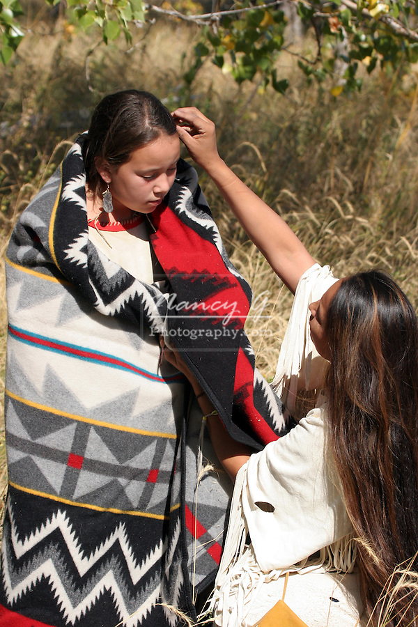 A young Native American Sioux Indian mother fixing the hair on her daughter wrapped in an Indian Blanket