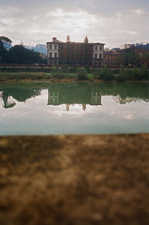Looking across river Arno to large urban building