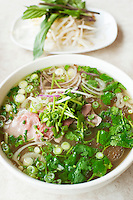 A bowl of herby Vietnamese beef noodle pho soup.