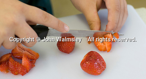 Chopping strawberries when making cupcakes, Food Technology class, state secondary School.
