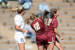 03 November 2013: North Carolina's Kelly McFarlane (11) heads the ball over Boston College's Jana Jeffrey (12) and McKenzie Meehan (22). The University of North Carolina Tar Heels hosted the Boston College Eagles at Fetzer Field in Chapel Hill, NC in a 2013 NCAA Division I Women's Soccer match and the quarterfinals of the Atlantic Coast Conference tournament. North Carolina won the game 1-0.