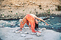 Woman in yoga pose by a flowing river.