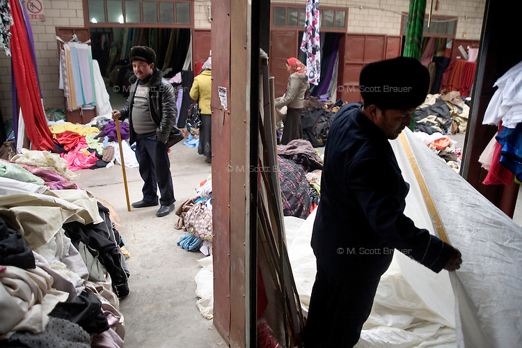 Uighurs shop for silk and other textiles in a market in Kashgar, Xinjiang, China.
