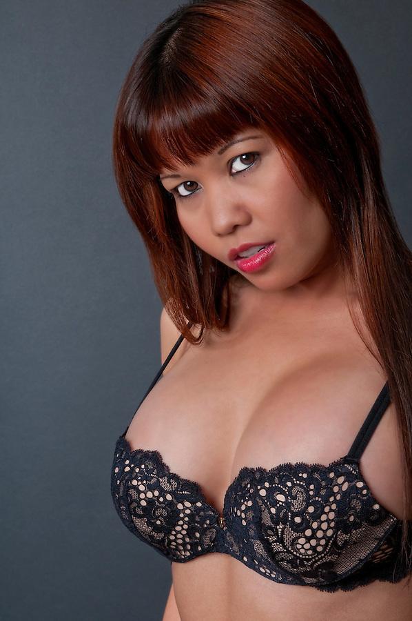 Sensual asian model posing in black lingerie.