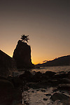 Rock jutting out of the sea silhouetted against the sky and cliffs. Stanley park, Vancouver,British Colombia, Canada.