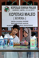 Fatni Lagora with a male customer at a village-run shop (BUMDes) selling agricultural supplies, Sausu Peore, Central Sulawesi, Sulawesi, Indonesia.