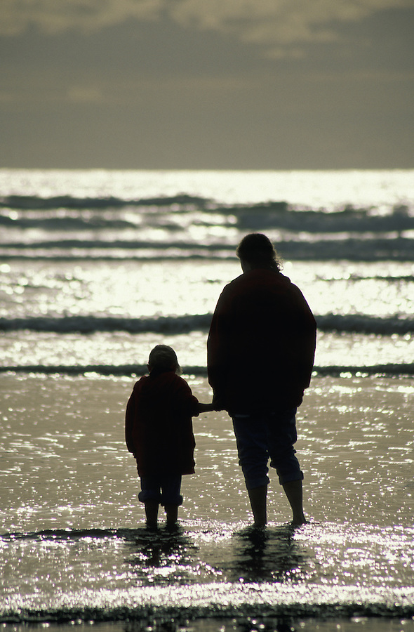 Woman and girl standing in ocean waves