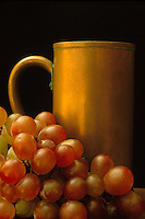 Antique copper mug beside rich red copper grapes
