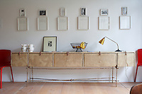 Framed images on wall above designer sideboard with lamp and fruit bowl