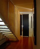 Wood veneer panels encase the staircase in this narrow hallway