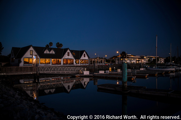 A restaurant with warm glowing windows is reflected in the waters of the San Leandro Marina along San Francisco Bay's eastern shore.