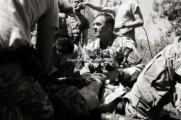 US Staff Sergeant Peter Rohrs (C), a medic working on a Medivac helicopter, treats an unidentified US soldier from White Platoon, Able Company, 3/71 Cav, 10th Mountain Division, following an ambush near Kamu outpost in Nuristan Privince, north-east Afghanistan, 14 May 2007. Elements of White Platoon were called upon, along with US Embedded Tactical Trainers (ETTs) and ANA from 1st Company, 2nd Kandak, 201st Corps, Afghan National Army, to act as a Quick Reaction Force to a nearby earlier ambush, but minutes after coming accross the first of the dead and wounded they were engaged by insurgents heavily dug into the mountainsides and got caught up in a major firefight. By the end of the day there were 15 ANA dead, 4 wounded, and one believed captured by insurgents. 6 US personnel and 1 Irish photographer were also wounded during the fight. (John D McHugh)