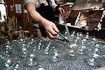 "Yutaka Shinohara removes traditional wind chimes, known as ""Edo furin,"" that he has just blown in his workshop at Shinohara Furin Honpo in Tokyo, Japan. The craft dates back more than 300 years in Japan, and is a common sound in the summer, thought to bring mental coolness on a steamy hot summer's day."