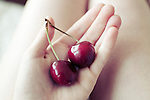 Close up of ripe red cherries with stalks on a girls hand