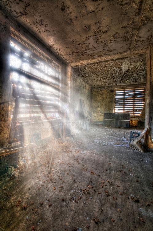 Sunlight shining through broken window in old tanks barracks somewhere near Berlin.
