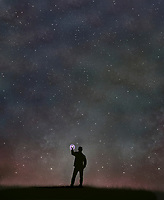 Man photographing starry sky with camera phone