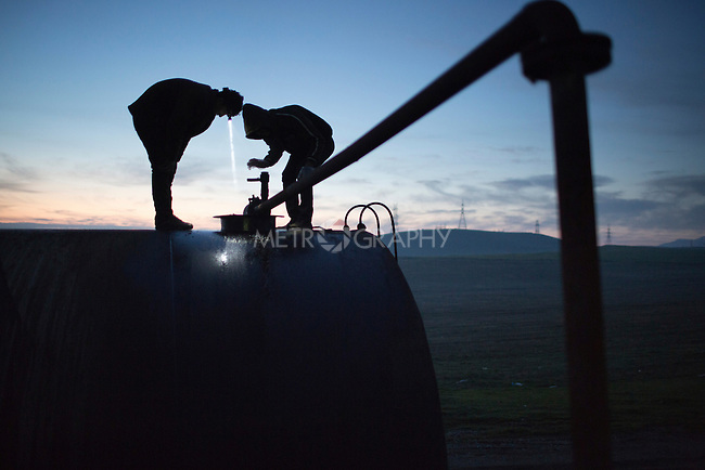 19/02/15 --TANJERO, IRAQ: Jamal (17) and Azdar (16) watch as fuel oil is pumped into a storage drum at dawn.<br /> <br /> Both boys were displaced from Sinjar by ISIS. They now live next to an oil refinery in the Kurdistan Region of Iraq which they run 24 hours a day with little to no safety equipment. Reporting for this article was supported by a grant from the Pulitzer Center on Crisis Reporting