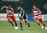 Two goal scorer Andy Najar #14 of D.C. United breaks away from Edson Edwards #27 and Bruno Guarda #8 of F.C. Dallas during a US Open Cup match on April 28 2010, at RFK Stadium in Washington D.C. D.C. United won 4-2.