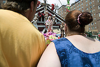 A man and a woman take a closer look at a statue of Christ that rests in a small shrine on Jackson and Third streets in Hoboken, NJ, USA, to examine the eye that is said to have suddenly opened without human intervention a few days earlier in what locals believe is a sign from God, 31 July 2005. Photo Credit: David Brabyn