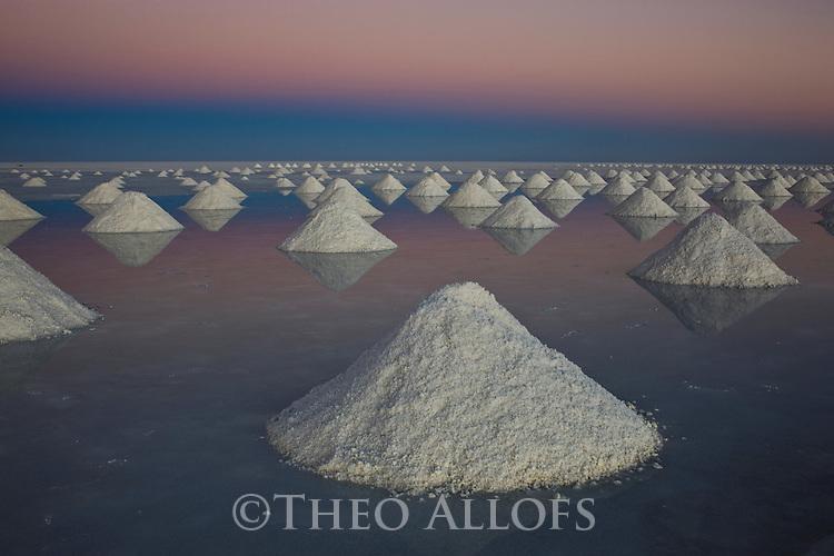 Bolivia, Altiplano, Salar de Uyuni, artificial salt mounts in Salar de Uyuni, largest salt pan in the world; the salt has been shoveled to mounts by salt workers for the salt to dry; sunrise