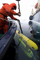 Submersible robots being placed under Arctic Ocean.