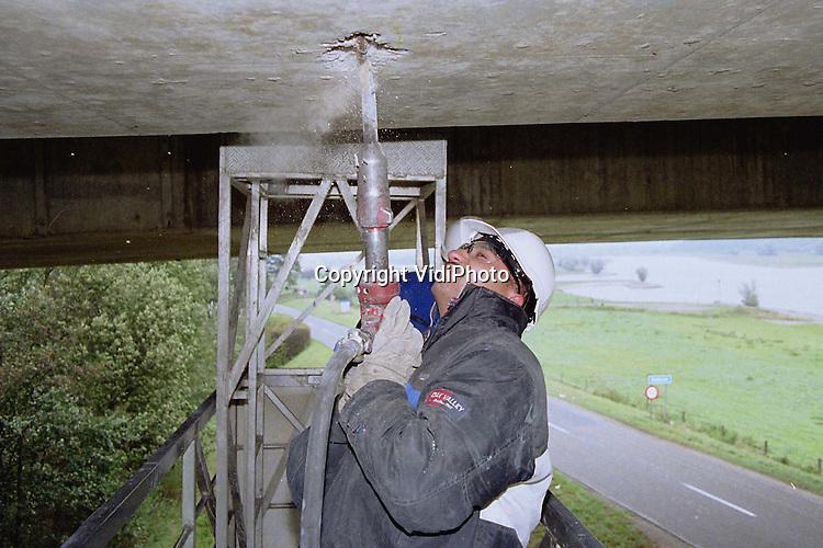 Foto: VidiPhoto..HETEREN - In opdracht van Rijkswaterstaat wordt de onderkant van de Rijnbrug in de A50 bij Heteren op dit moment grondig aangepakt. Via een zogenaamde laagwerker klimmen de bouwvakkers onder de brug om met een drilboor de rotte plekken in het beton weg te hakken. Om verdere betonrot te voorkomen worden de uitgedrilde plekken direct weer aangesmeerd met een verse laag beton. De werkzaamheden zijn onderdeel van de totale .reconstructie van de Rijnbrug, die ongeveer 8 miljoen gulden kosten..