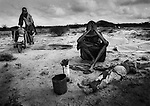 A Somali woman weeps for a young male relative about to be buried, Baardheere, Somalia. November 1992