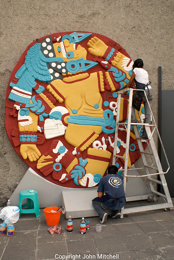 Painters working on a replica of the circular stone depicting the dismembered Aztec goddess Coyolxauhqui, Museo del Templo Mayor, Mexico City