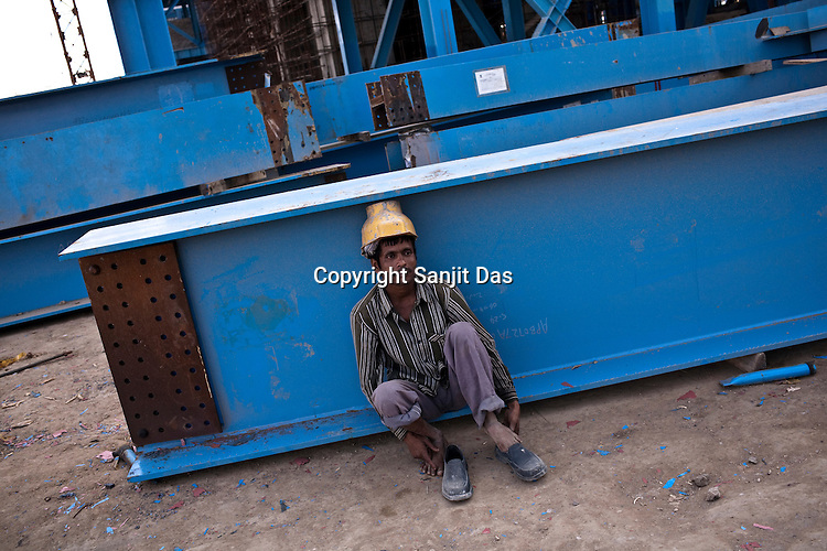 An Indian worker is seen at the construction site of the Adani Power plant in Mundra port industrial city of Gujarat, India. Indian power companies have handed out dozens of major contracts to Chinese firms since 2008. Adani Power Ltd have built elaborate Chinatowns to accommodate Chinese workers, complete with Chinese chefs, ping pong tables and Chinese television. Chinese companies now supply equipment for about 25% of the 80,000 megawatts in new capacity.