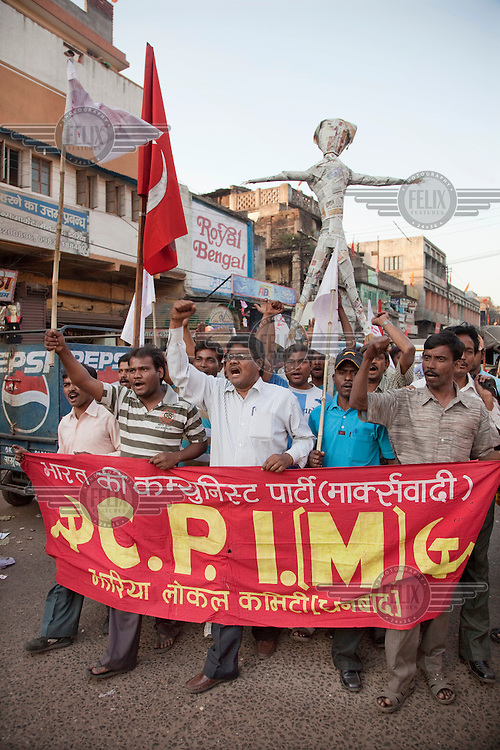 Demonstrators march through the outskirts of Dhanbhad, the centre of Jharkhand's coal mining industry. They carry a banner of the C.P.I.(M), the Communist Party of India (Maoist), who are still engaged in peaceful protest and electoral politics, as opposed to the Naxalites, militant Maoists who are fighting to overthrow the Indian state. The protest was against a recent rise in food prices and also to highlight the problem of coal fires that are burning across the region, destroying roads, villages and agricultural land. The government is accused, along with coal mining companies, of deliberately letting the coal fires burn out of control in order to force people off land sought by mining companies.