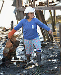 A woman cleans up debris in Tacloban, a city in the Philippines province of Leyte that was hit hard by Typhoon Haiyan in November 2013. The storm was known locally as Yolanda. She is a participant in a United Nations funded cash for work program.