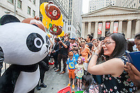 """Costumed characters representing Line """"stickers"""" in front of the New York Stock Exchange decorated for the Japanese messaging company Line's initial public offering on Thursday, July 14, 2016. Line Corp., a popular messaging app in Japan is owned by South Korean Naver Corp. Line has 218 million active users monthly, with Japan, Taiwan and Indonesia accounting for two-thirds of them.   (© Richard B. Levine)"""