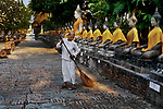 00559_02, Footsteps of Buddha, Ayutthaya, Thailand; 2004; THAILAND-10019. An adherence of Buddhism sweeps a walkway lined with statues.