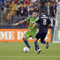 Seattle Sounders defender Zach Scott (20) dribbles under pressure. In a Major League Soccer (MLS) match, the Seattle Sounders FC defeated the New England Revolution, 2-1, at Gillette Stadium on October 1, 2011.