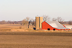 The early morning sun accents a red barn in the middle of a plowed field in North Central Illinois.