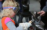 Foto: VidiPhoto<br /> <br /> OOSTERBEEK - Feestvierders lieten zich woensdag tijdens Koningsdag niet afschrikken door de korte, maar soms hevige regen- en hagelbuien. Bij de Oranjemarkt in Oosterbeek, traditioneel een kleedjesmarkt voor kinderen, waren kramen geplaatst waaronder de activiteiten tijdens de regen gewoon doorgingen. Wel waren de meeste mensen vanwege de kou goed aangekleed, maar volgens de organisatie was het nauwelijks minder druk dan andere jaren. Foto: Leren smeden op de Oranjemarkt.